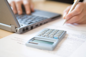 Woman using laptop and calculator close up