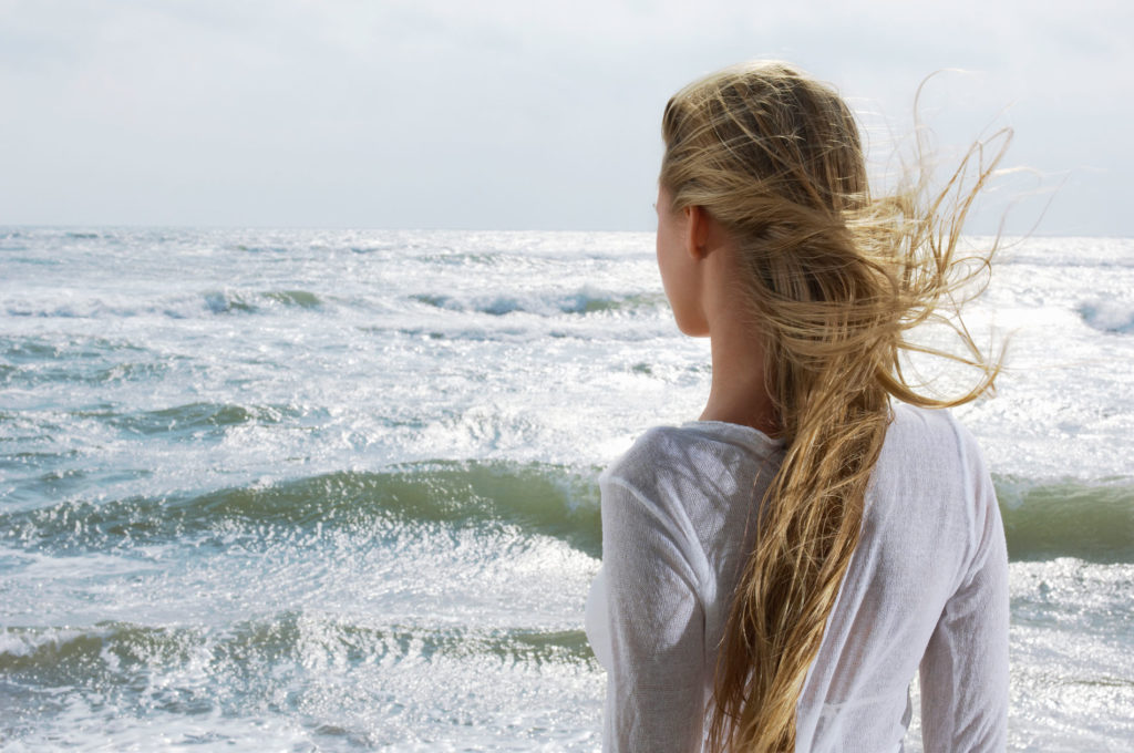 Young woman looking at ocean back view